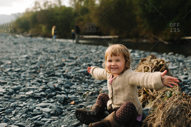 Smiling young girl sitting on river shore with outstretched arms