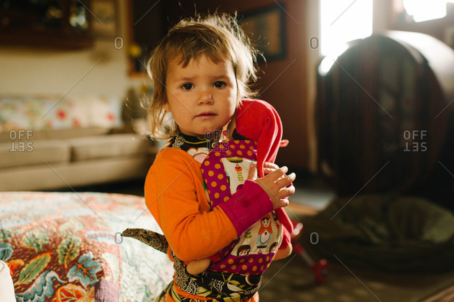 Little girl standing with baby carrier