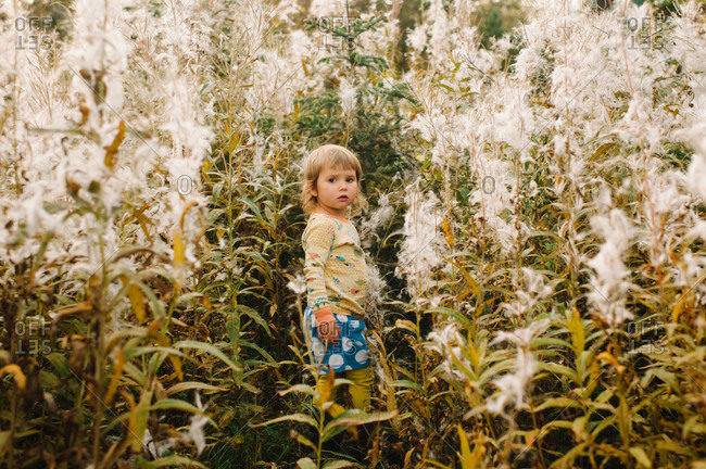 Young girl standing among high plants