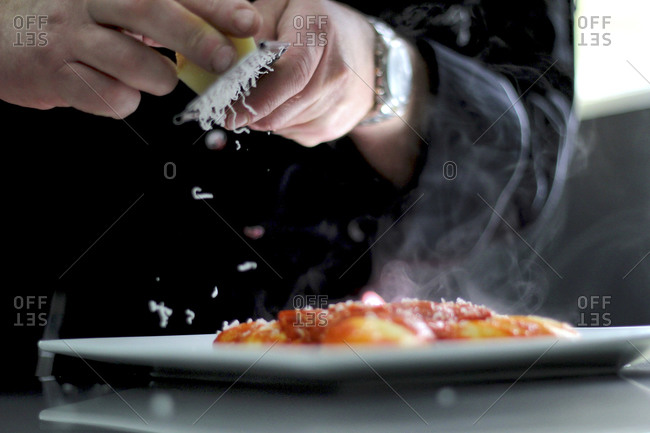 Close up of person grating cheese over a pasta dish