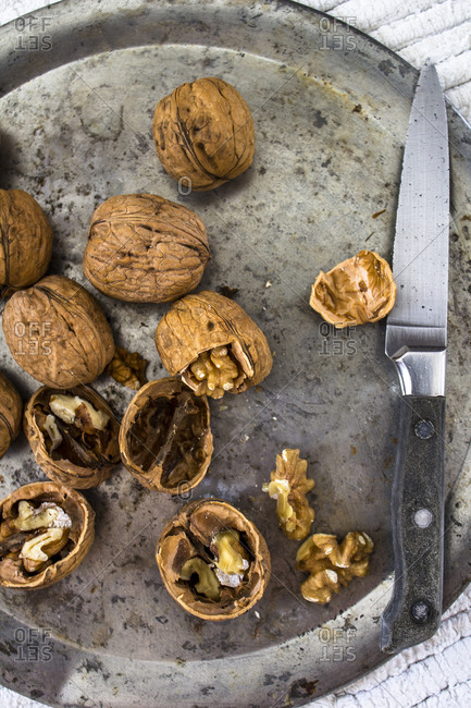 Cracked walnuts with a knife on a plate