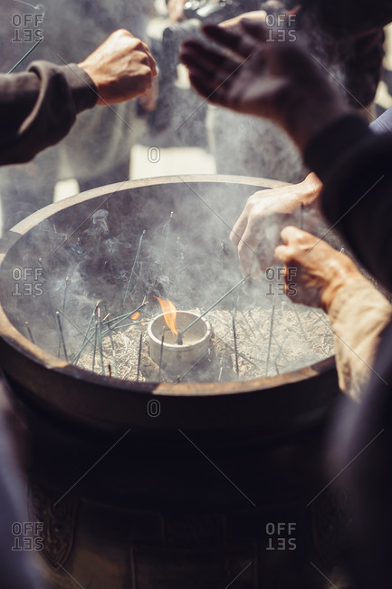 People burn incense in a large drum