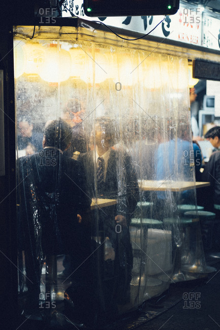 Tokyo, Japan - April 2, 2014: Businessmen sit behind a tarp in an outdoor restaurant