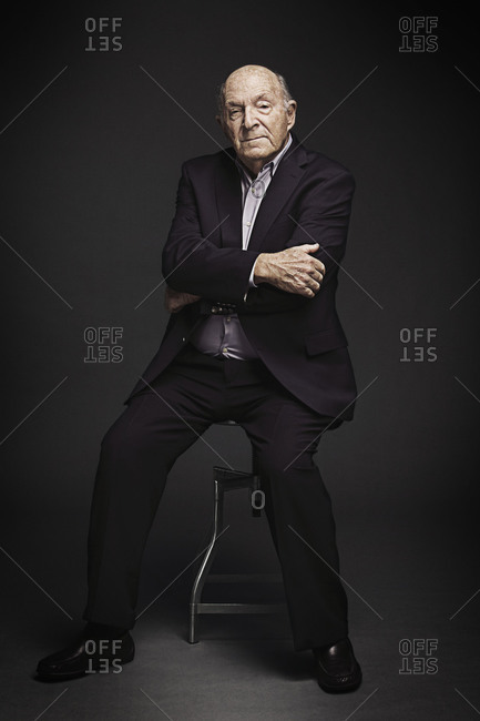 Portrait of elderly man sitting on a stool