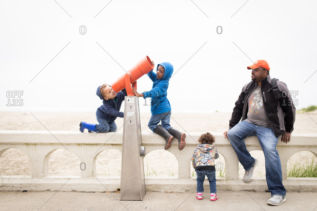 Children playing with an outdoor viewer next to their father