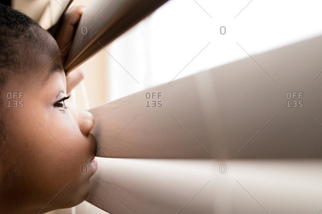 Boy peeking through blinds