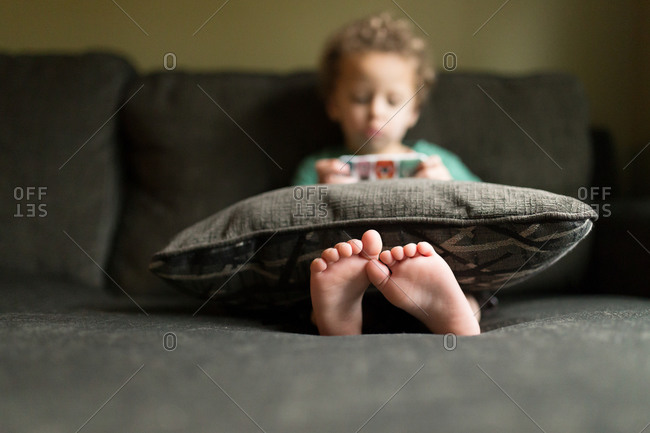Toddler boy playing game on phone with feet sticking out