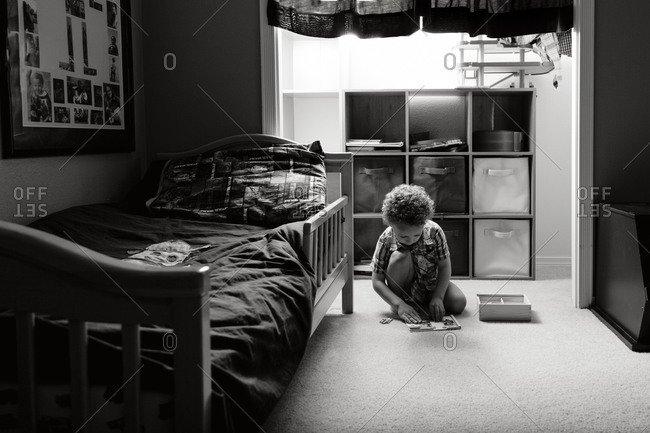 Young boy playing on bedroom floor by light of the closet