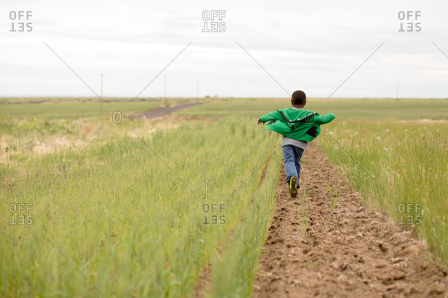 Young boy running through field with jacket billowing