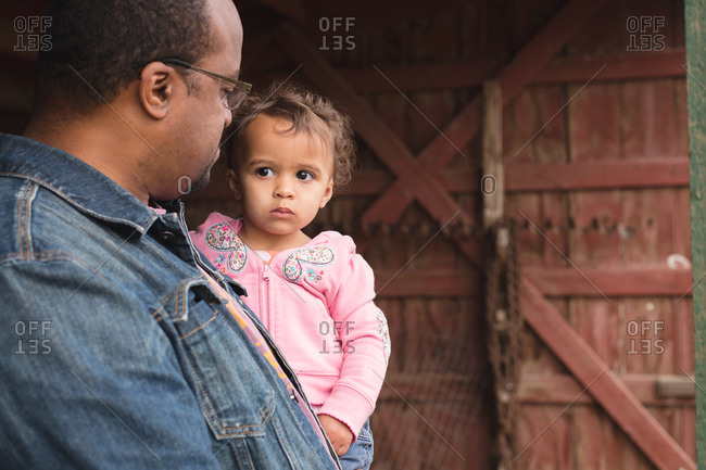 Father holding apprehensive toddler girl