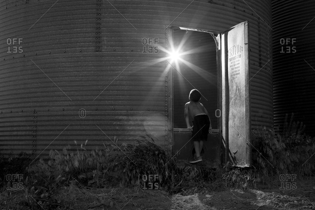 Rear view of young shirtless boy looking into grain silo with starburst
