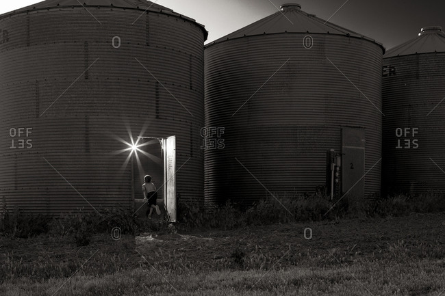 Far away shot of young boy looking into grain silo with starburst