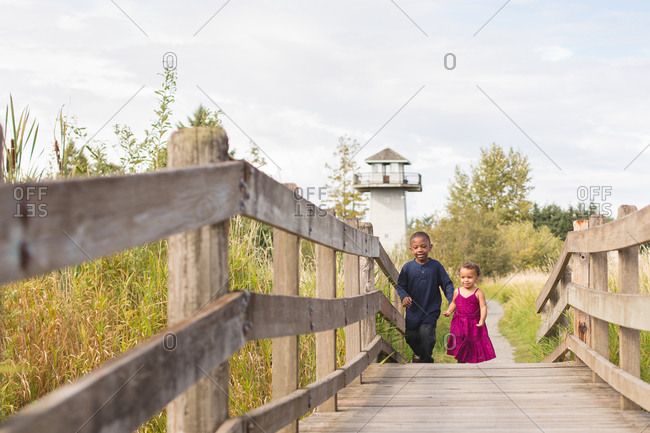 Young boy and toddler sister walk over a bridge in a park