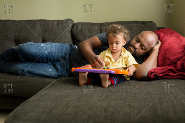 Father helps toddler daughter draw on tablet