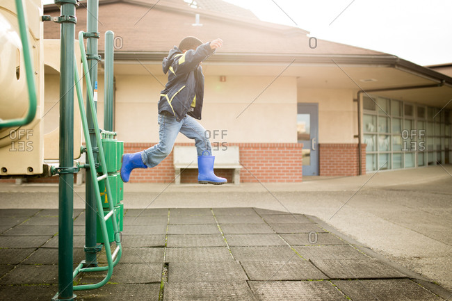 Young boy leaps off school playground