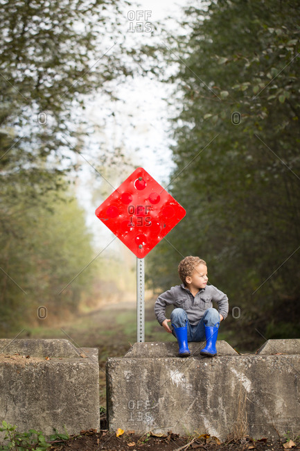 Young boy in boots on country land with red sign