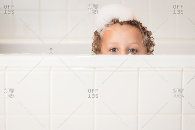 Young boy in bubble bath peeks over edge of tub