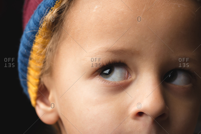 Close up of young boy in striped hat looking up