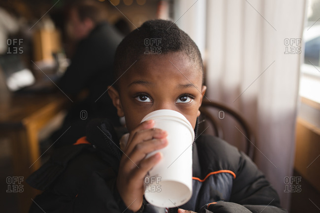 Boy drinking out of a white coffee cup