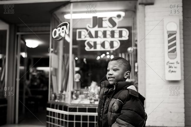 Boy smiling in front of barber shop