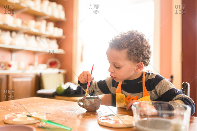 Boy decorating pottery with paint