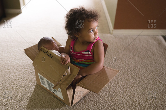 Girl sitting in a box with her doll