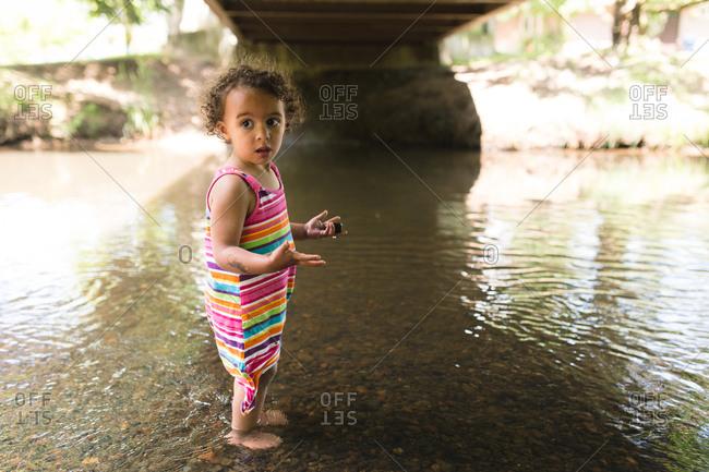 Little girl collecting pebbles under a bridge