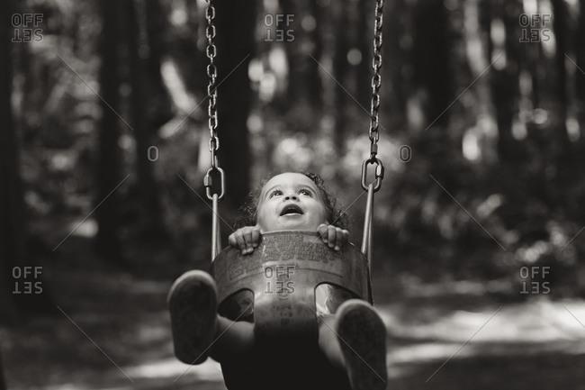 Little girl sitting in a swing