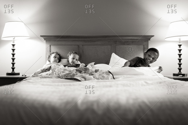Siblings lying in a bed together