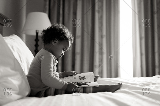 Little girl reading a comic book in bed