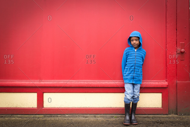 Boy standing by a red wall