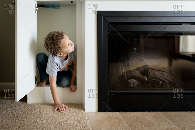 Boy climbing out of a cabinet