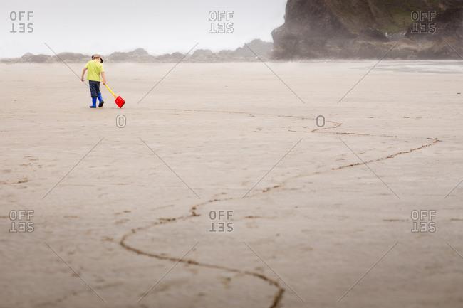 Boy dragging a toy shovel along the beach