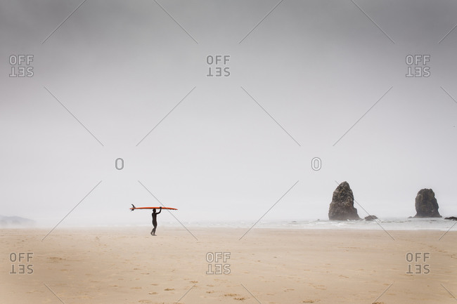 Man carrying a surfboard on the beach
