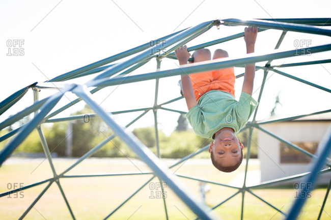 Young boy hanging from a jungle gym at a playground