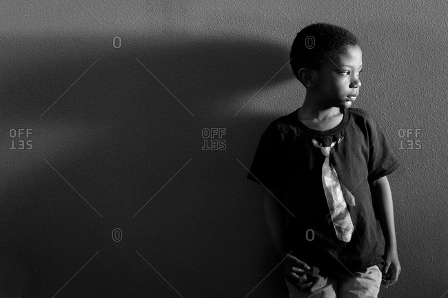 Portrait of a boy leaning against a wall
