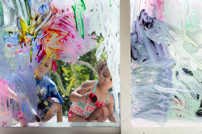 Children painting on a window glass