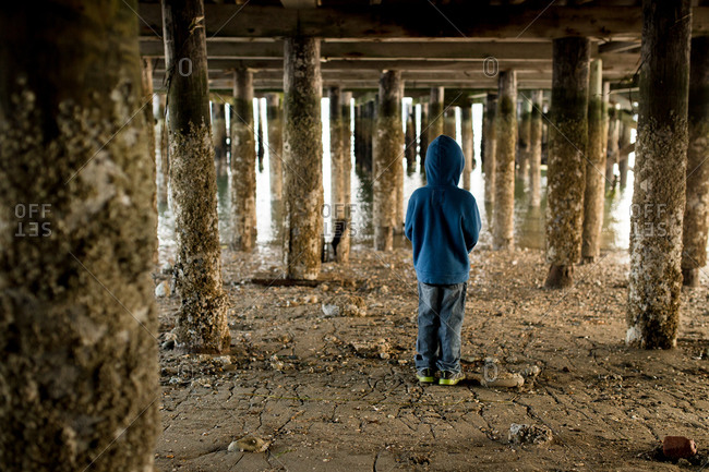 Young boy standing under a dock