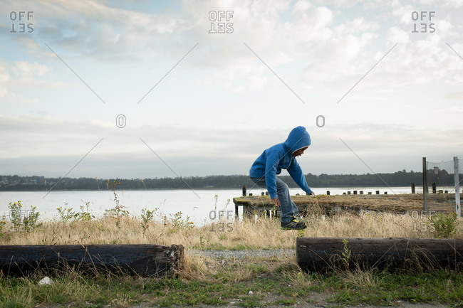 Young boy jumping on logs