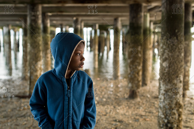 Portrait of a young boy standing under a dock