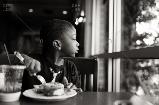 Young boy staring out of a window while eating at a table