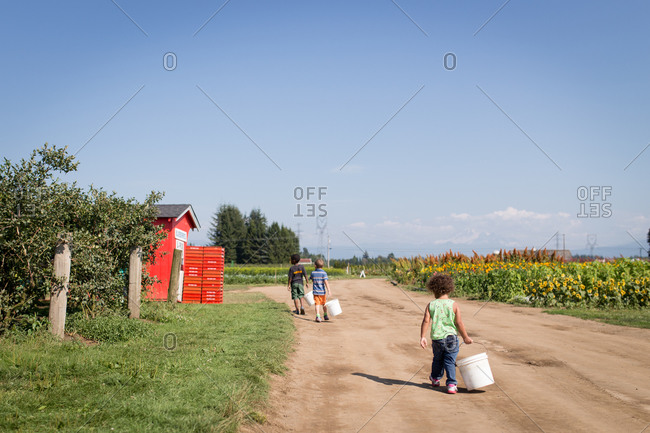 Children carrying buckets on a dirt road