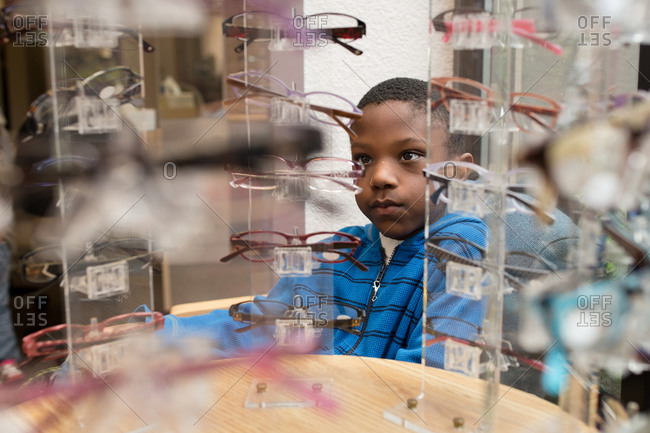 Young boy looking at an eyewear display stand