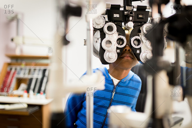 Young boy looking through a phoropter in a clinic