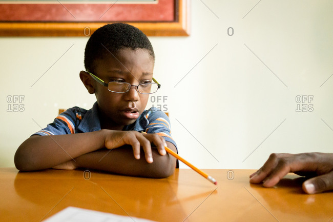 Upset boy holding a pencil at a table