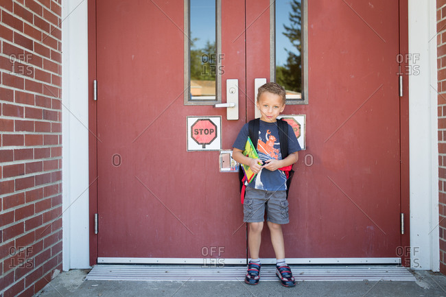 Young boy standing at the entrance of a school