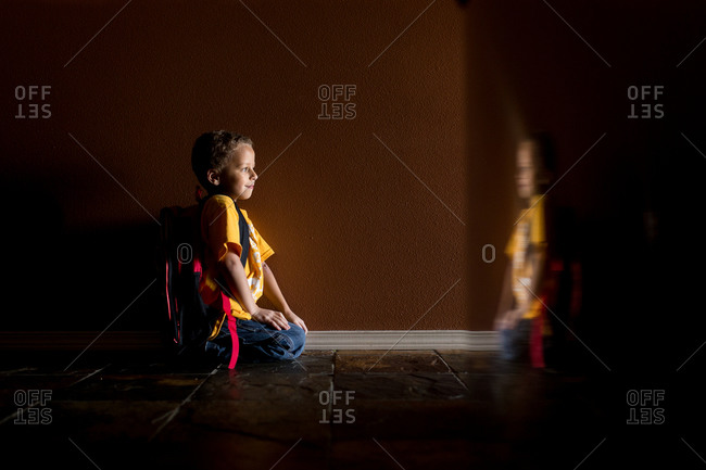 Young boy kneeling in a corridor