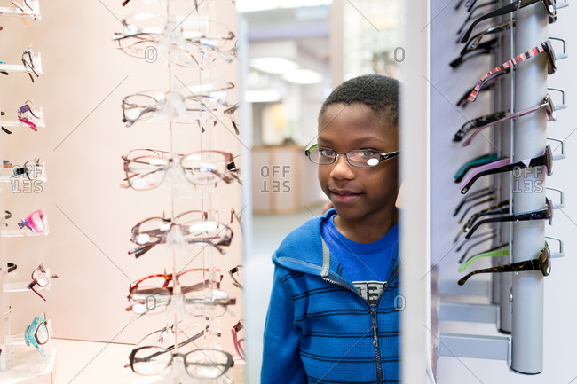 Young boy standing at eyewear display stands in a shop