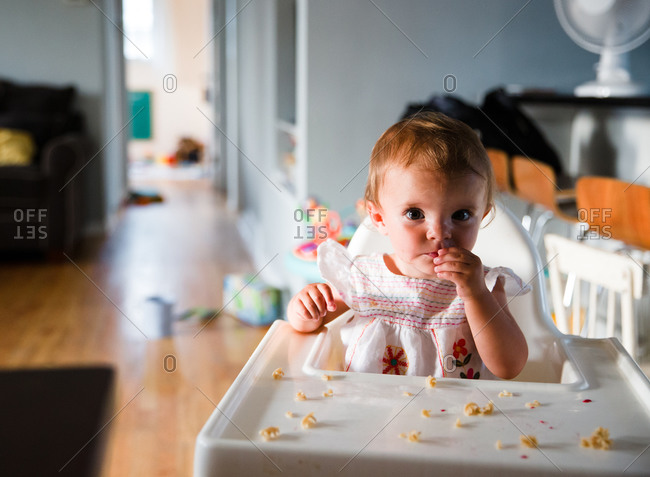 A baby eats noddles at a highchair