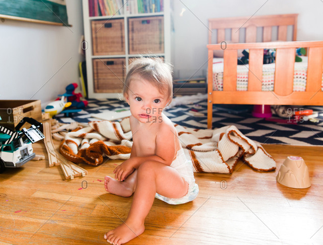 A baby sits on the floor among toys